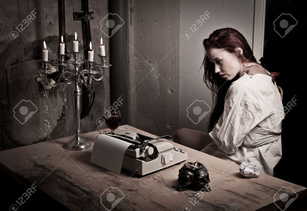 a mad girl wearing a straight jacket in front of a typewriter stock