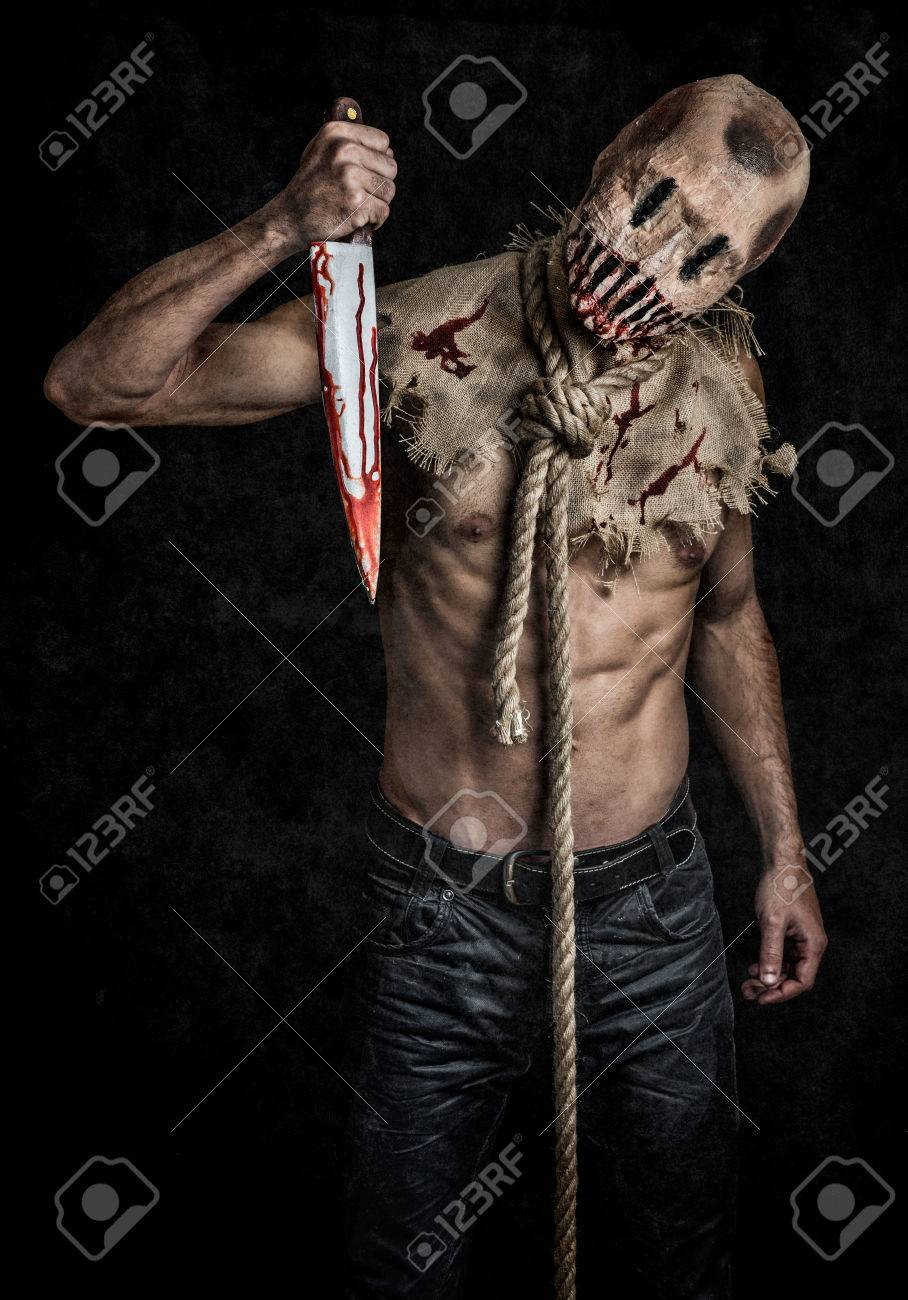 a scary looking scarecrow demon with a bloody knife Stock Photo - 33874744