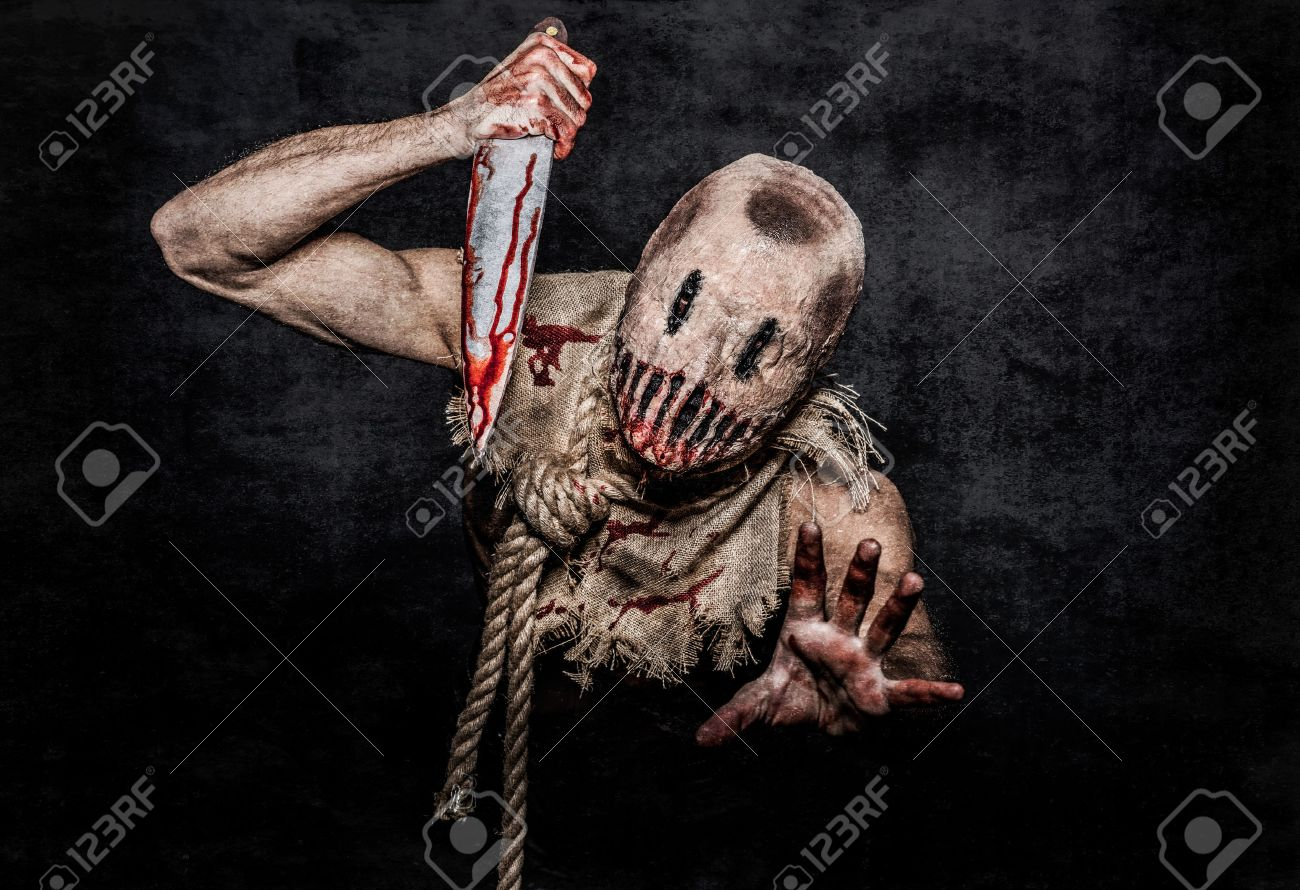 a scary looking scarecrow demon with a bloody knife Stock Photo - 33874751