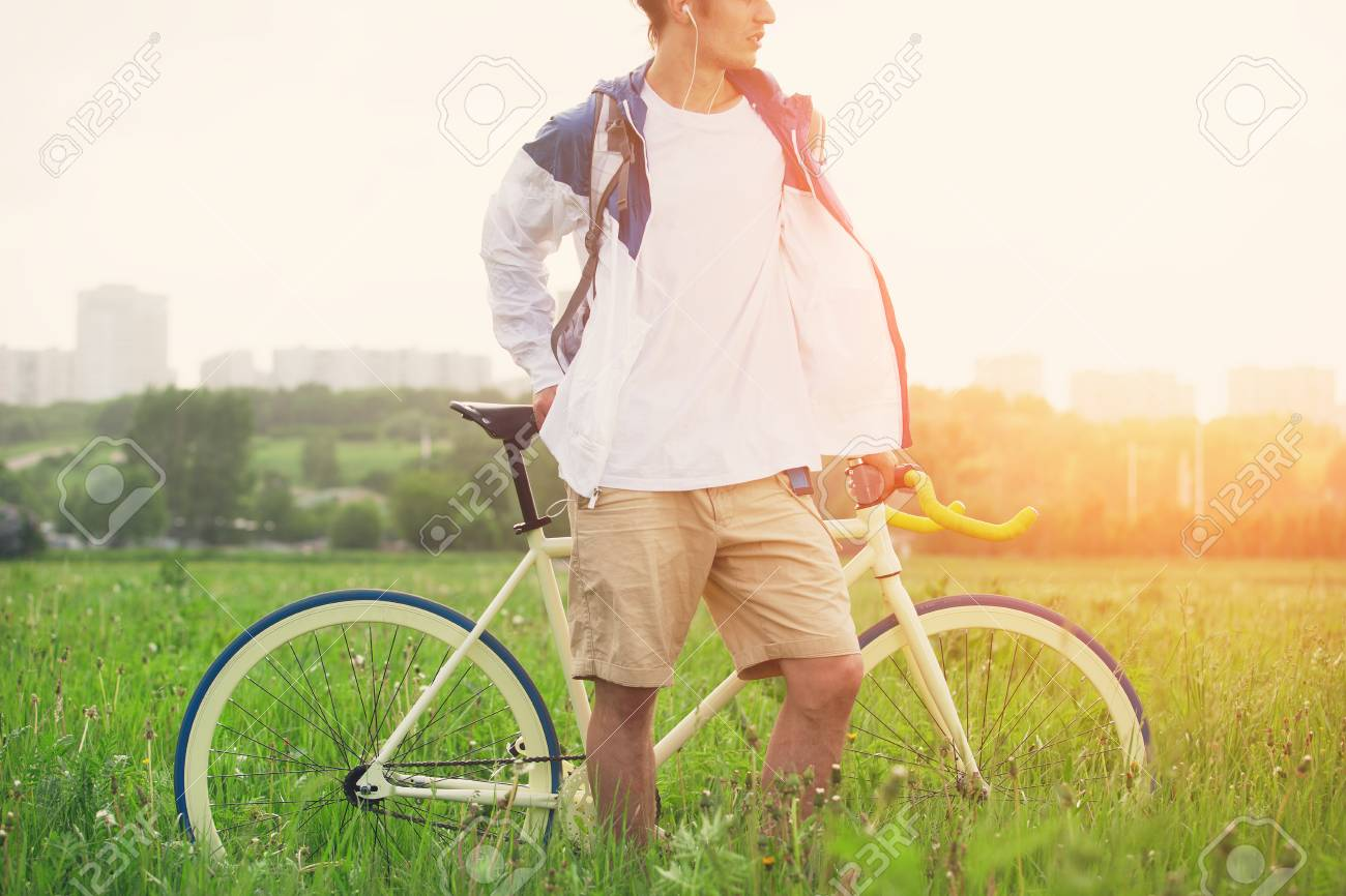 Man in blank t-shirt with bicycle standing in green field (intentional sun glare and bright color) Stock Photo - 85235908