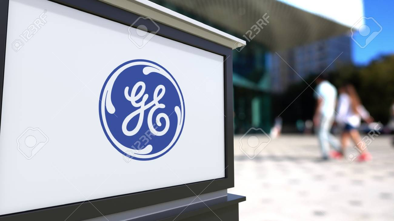 Street signage board with General Electric logo. Blurred office center and walking people background. Editorial 3D rendering United States - 65672928
