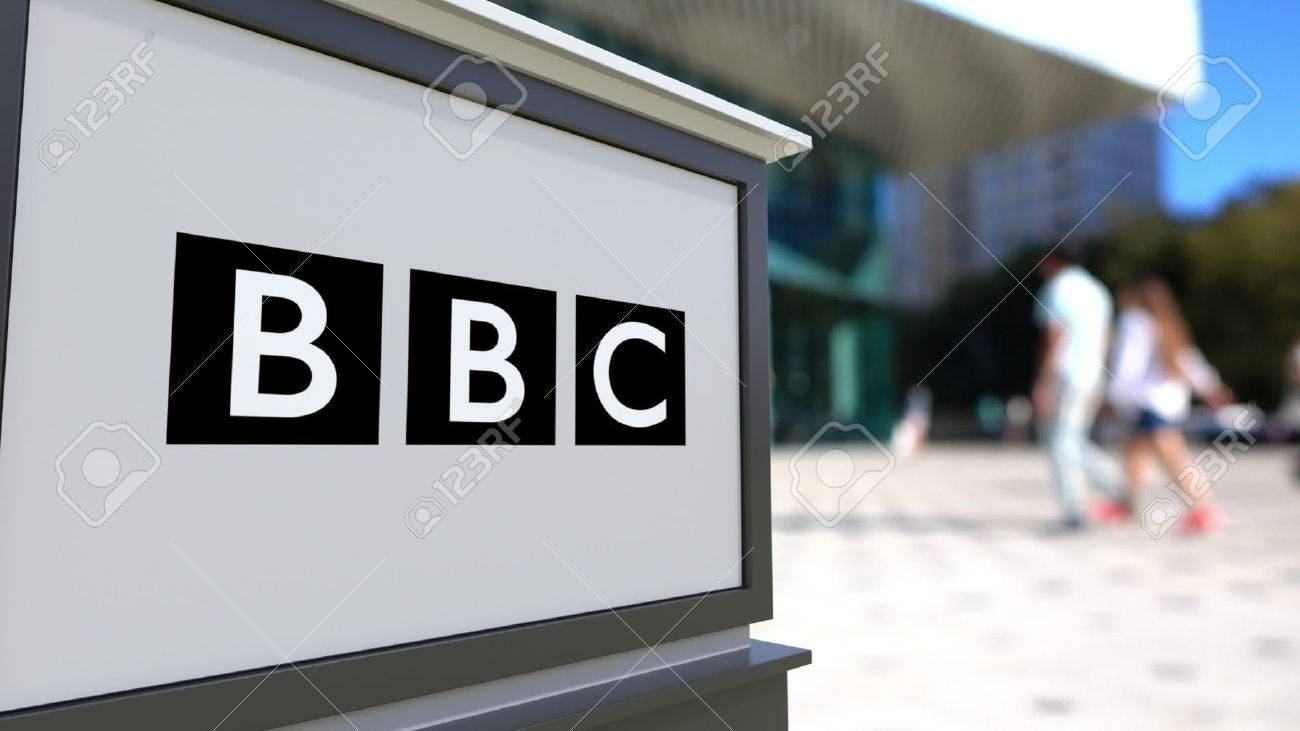 Street signage board with British Broadcasting Corporation BBC logo. Blurred office center and walking people background. Editorial 3D rendering - 71008234