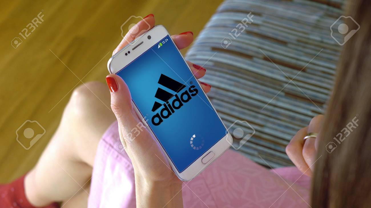 sports shoes 9be03 f4ac0 Stock Photo - Young woman holding a cell phone with loading Adidas mobile  app. Conceptual editorial CGI
