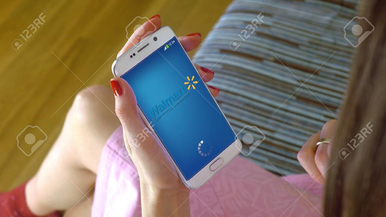 Walmart Stock Phone Number >> Young Woman Holding A Cell Phone With Loading Walmart Mobile Stock