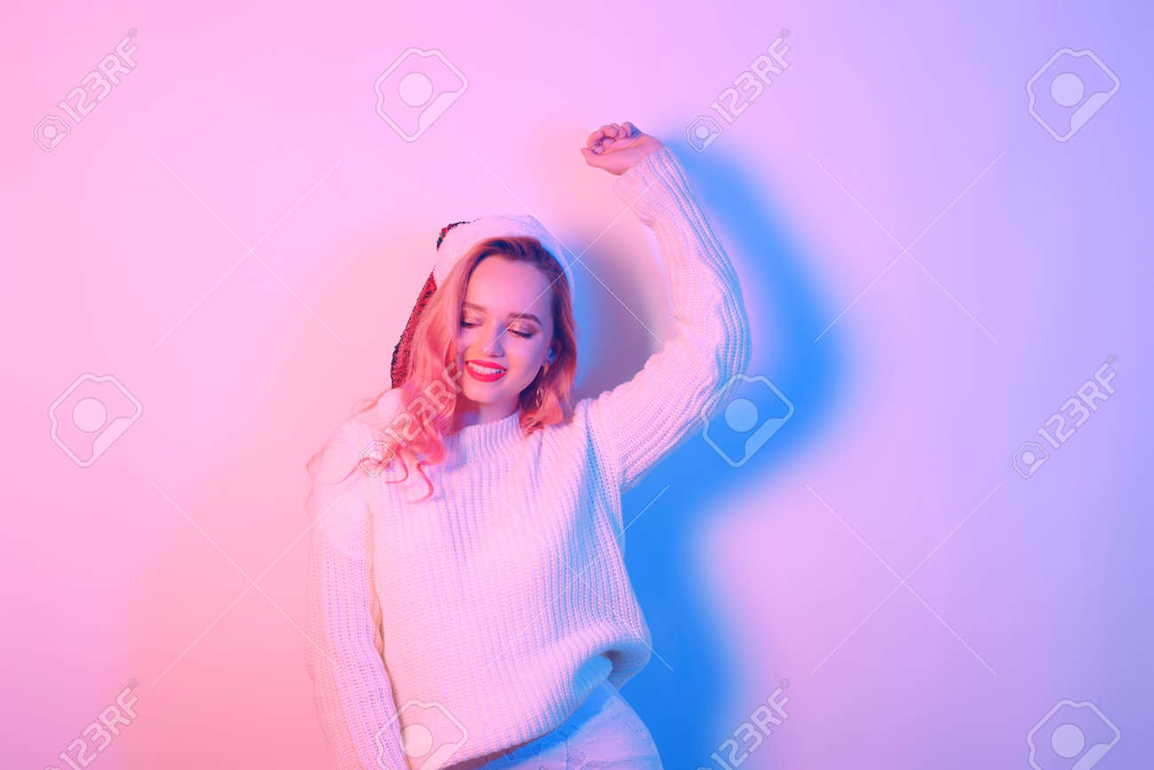 Girl in a white sweater and santa hat in neon light. Woman with professional makeup and red lips. Model with pink hair dancing. New Year Christmas. - 165918160