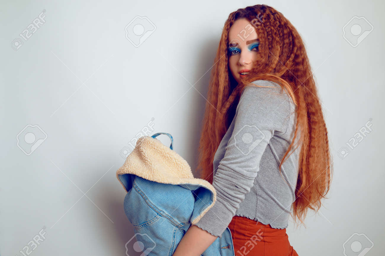 A girl with curled voluminous hair is dancing, a model in the style of the 80s. 90s, with bright blue make-up and a jacket. The girl on a white background sobazet, flirts. Fashion photo of a model in the old style. - 158812297