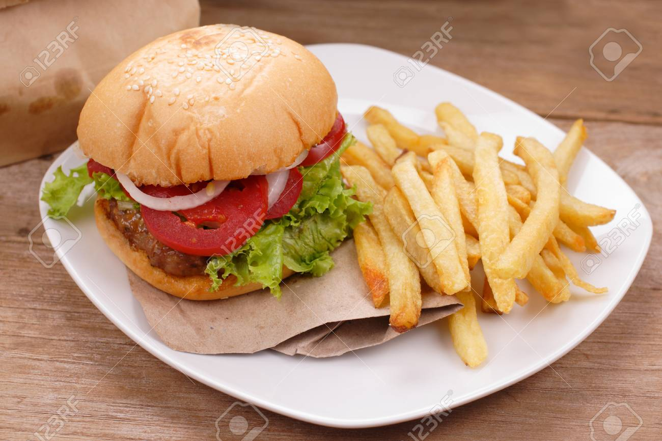 hamburger and french fries on wooden background - 64789958