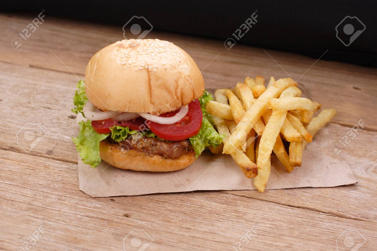 hamburger and french fries on wooden background - 64790376