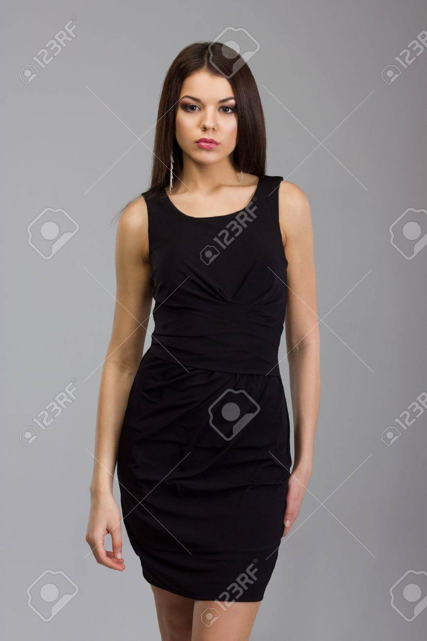 Beautiful woman standing in a black dress over gray background Stock Photo - 21465548