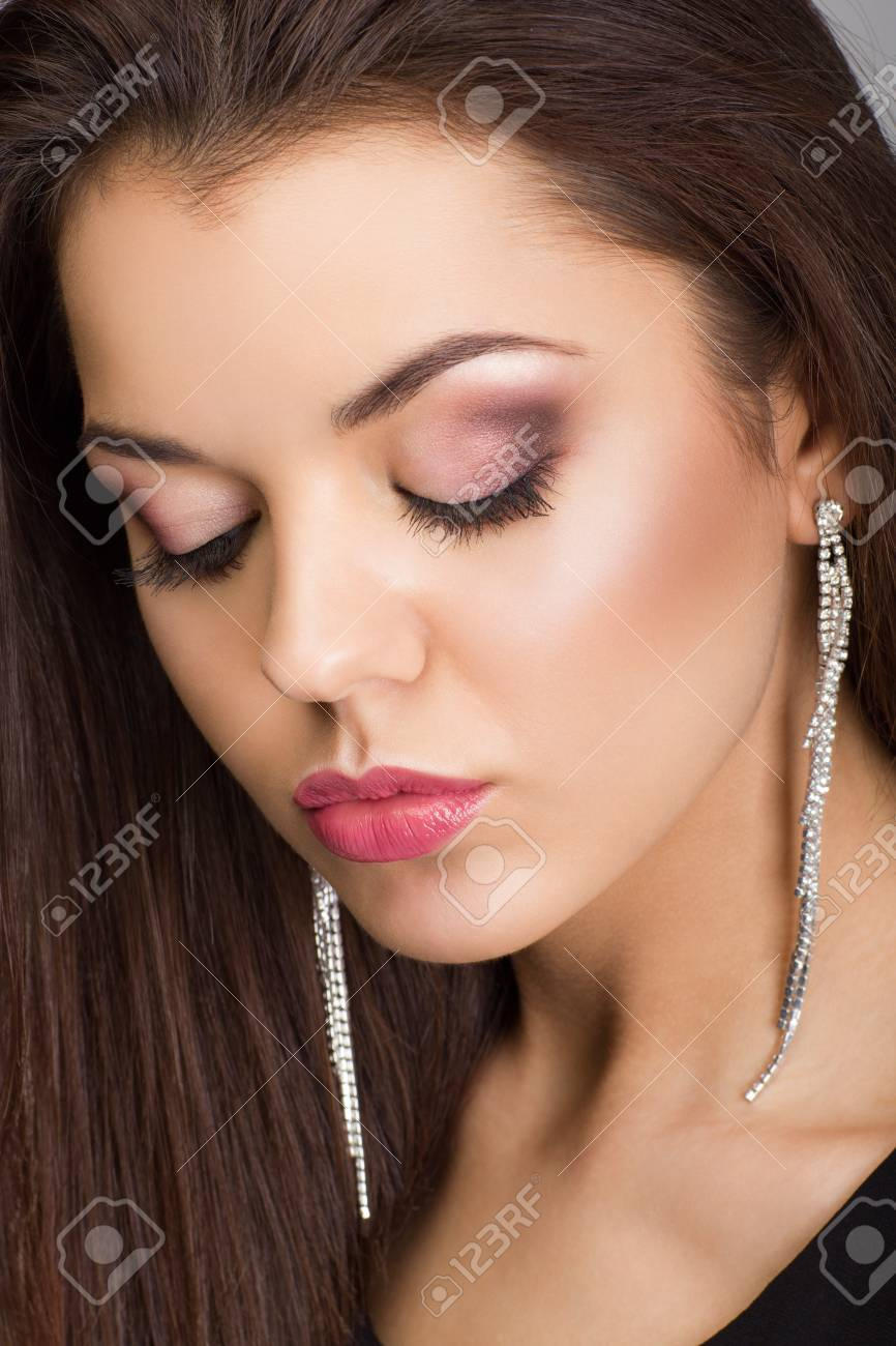 Portrait of a beautiful woman with evening make-up and earrings looking down Stock Photo - 21465552