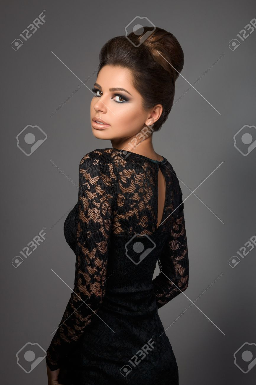 Black dress hairstyle - Beautiful Young Model In Black Dress With Evening Makeup And Hairdo Standing Back To Camera And