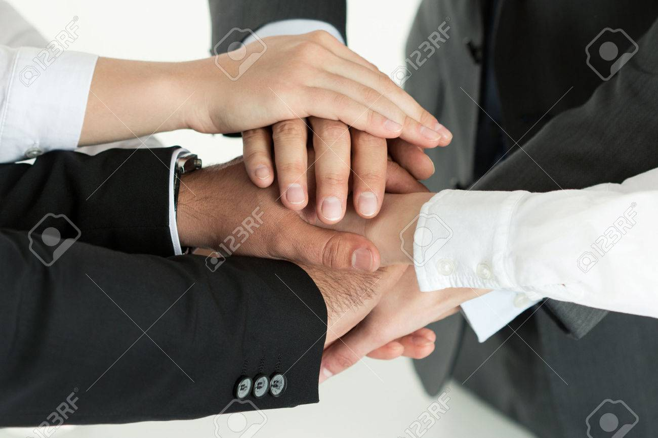Closeup of business team showing unity with putting their hands together on top of each other. Concept of teamwork. Stock Photo - 43206857