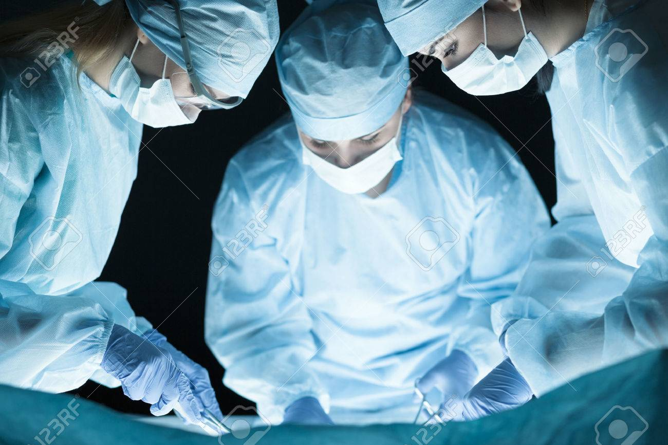 medical team performing operation group of surgeon at work in
