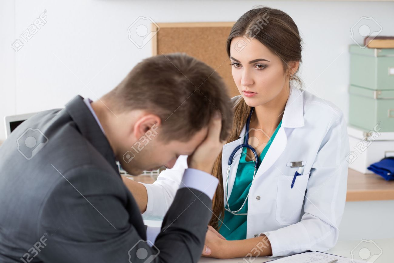 Friendly female medicine doctor's holding male patient's hand supporting him. Bad news, stress and depression concept. - 47974722