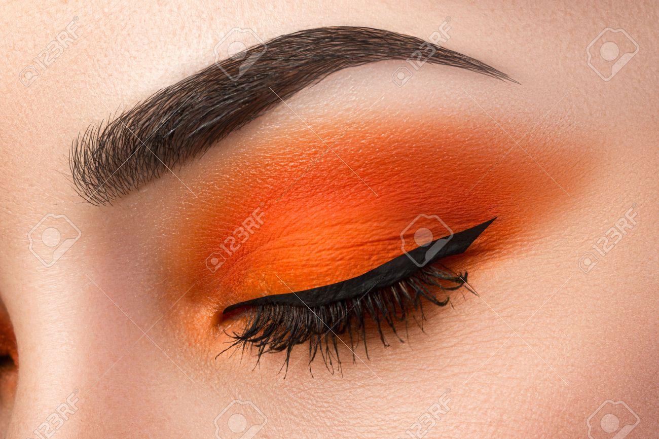 Close-up of woman eye with beautiful orange smokey eyes with black arrow makeup. Modern fashion make-up. - 49807793