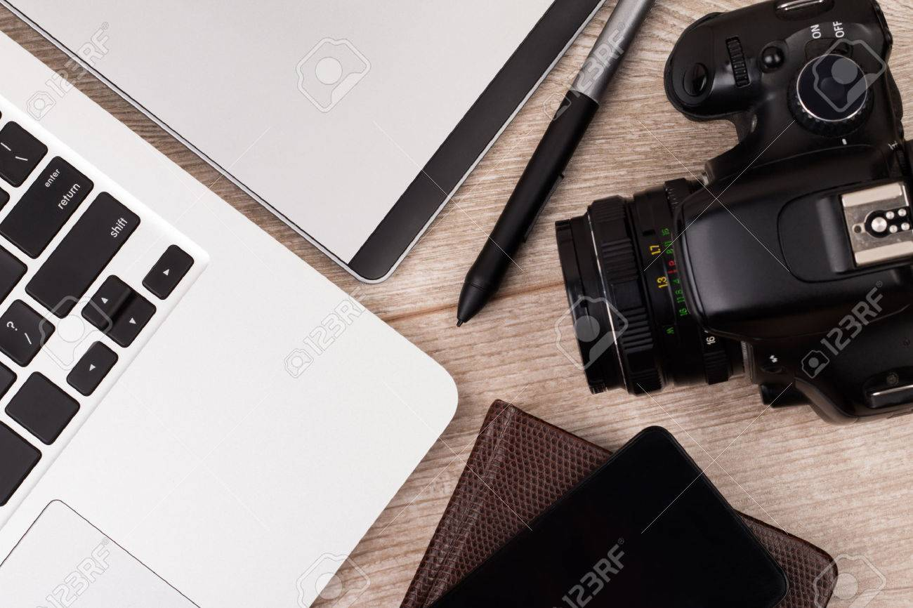 Close-up top view of photographer of graphic designer workplace. Laptop, graphic tablet, phone and photo camera on wooden table. - 54703811