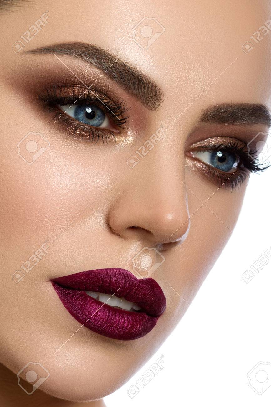 Close up portrait of young woman with wine red lips and bronze smokey eyes