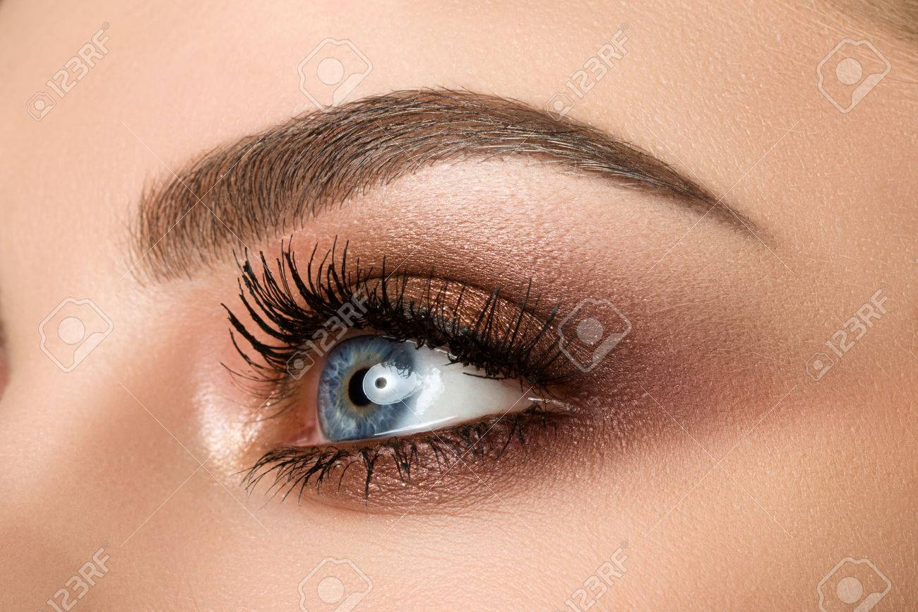 Close up of blue woman eye with beautiful brown with red and orange shades smokey eyes makeup. Modern fashion make up. - 56057664