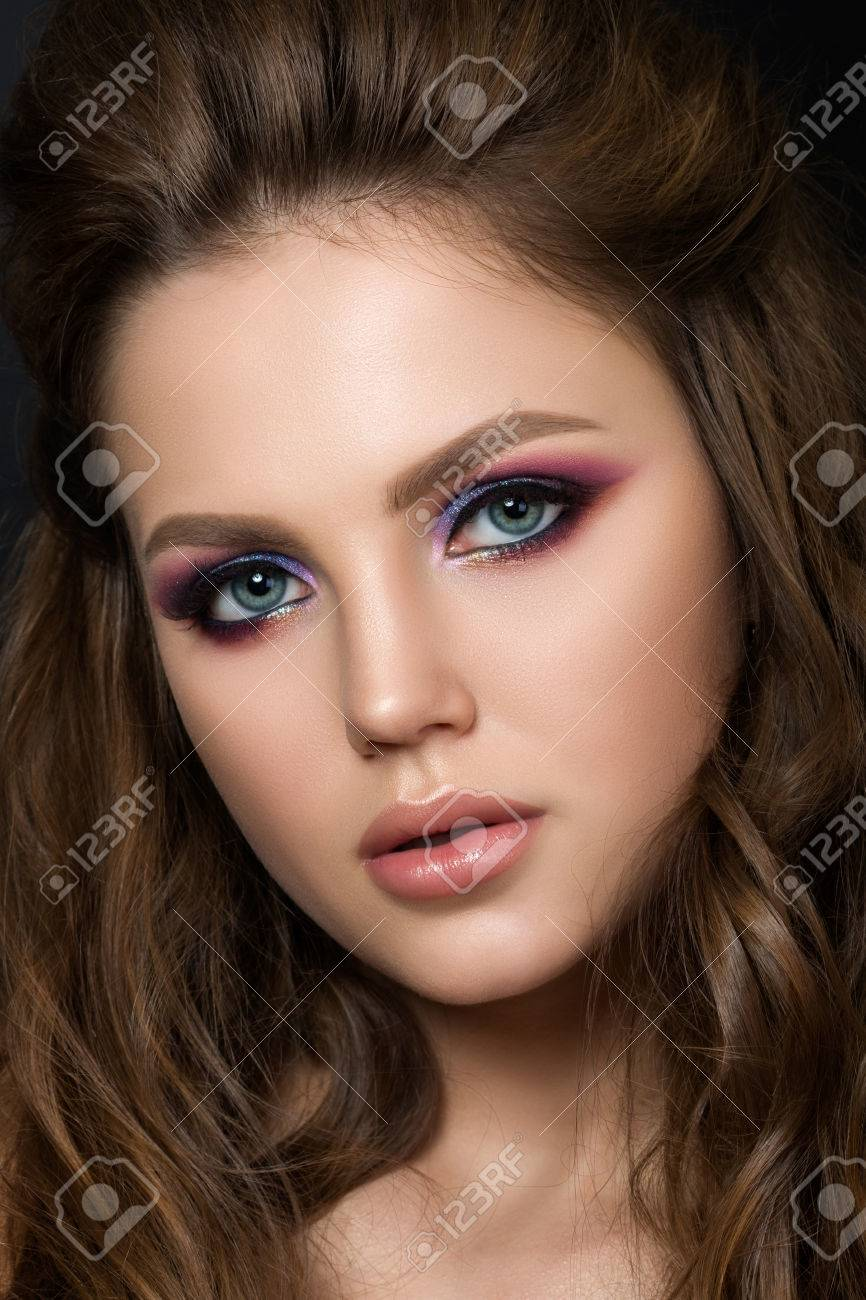 Close up portrait of young beautiful woman with purple evening make up over black background. Modern fashion smokey eyes makeup. Studio shot. - 56057666