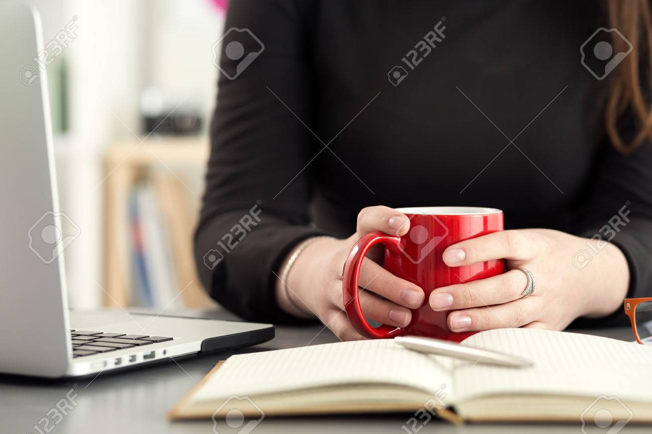Female designer in office drinking morning tea or coffee. Coffeebreak during hard working day. Girl holding cup of hot beverage. - 59198378