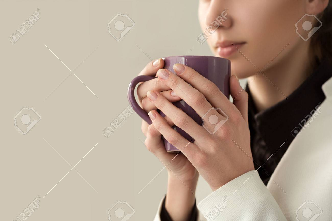 Close up of young beautiful woman hands holding hot cup of coffee or tea. Morning coffee, cold season, office coffee break or coffee lover concept. - 59198382