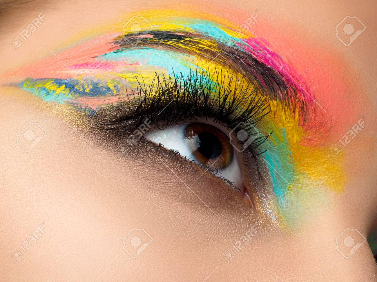 Close up of blue woman eye with beautiful brown with red and orange shades smokey eyes makeup. Modern fashion make up. - 72560482