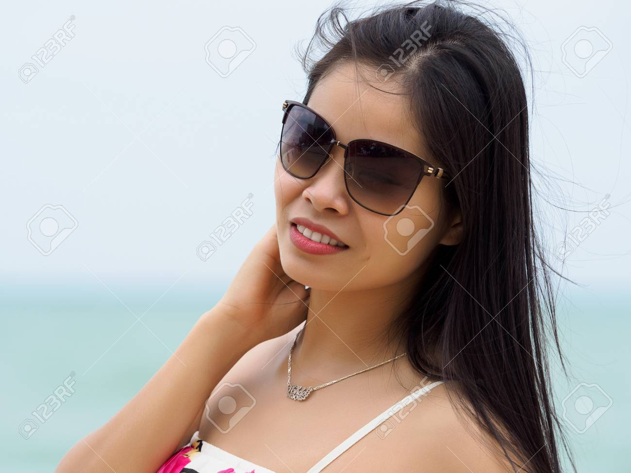 0302abb082 Portrait of young beautiful asian woman wearing sunglasses and standing on  the beach. Summer time