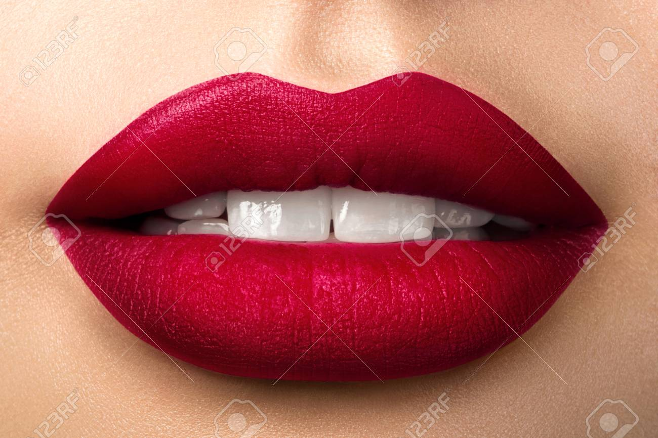 Close up view of beautiful woman lips with red matt lipstick. Open mouth with white teeth. Cosmetology, drugstore or fashion makeup concept. Beauty studio shot. Passionate kiss - 94965589