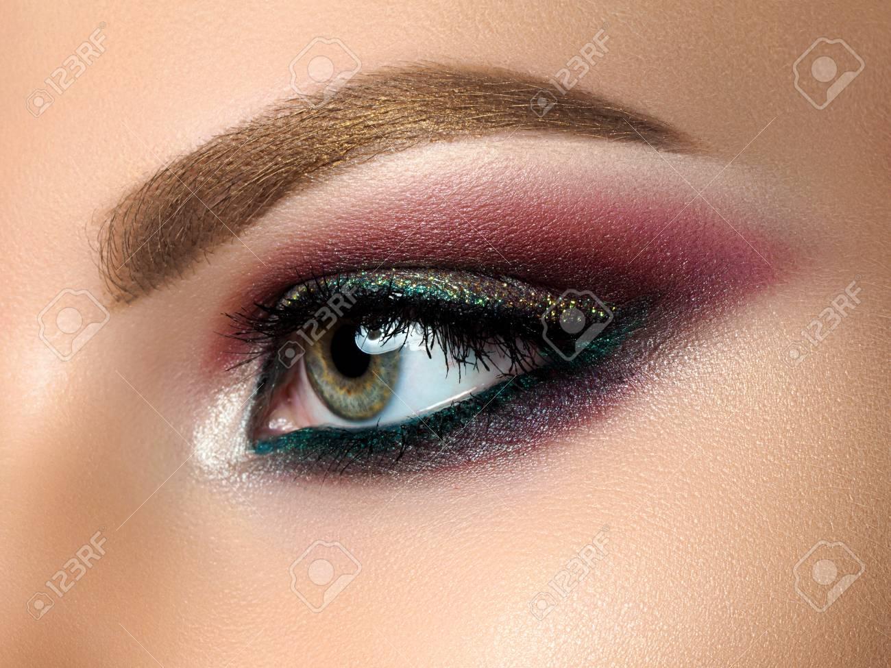 close up of beautiful woman eye with multicolored smokey eyes..