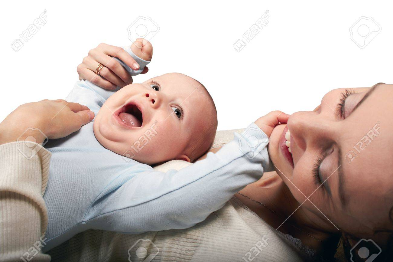 The dark-haired woman in a white jacket lies on a spin and holds on a stomach of the laughing baby. White background. Stock Photo - 19056113