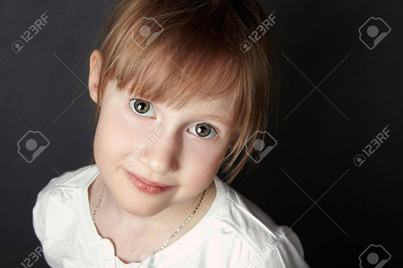 The green-eyed girl with freckles trustfully looks in the camera,black background Stock Photo - 19672426