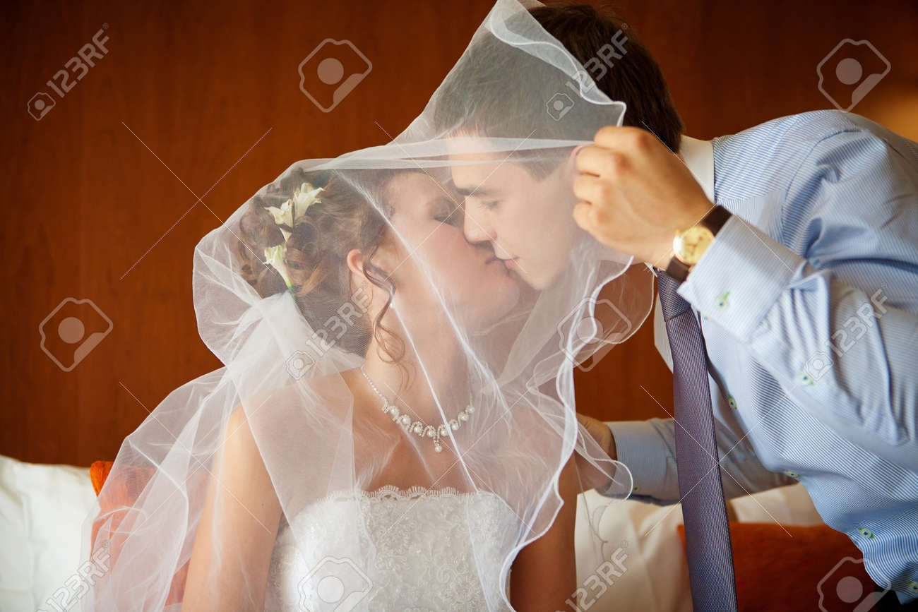 Newlywed couple kissing each other in the bedroom Stock Photo - 9688025
