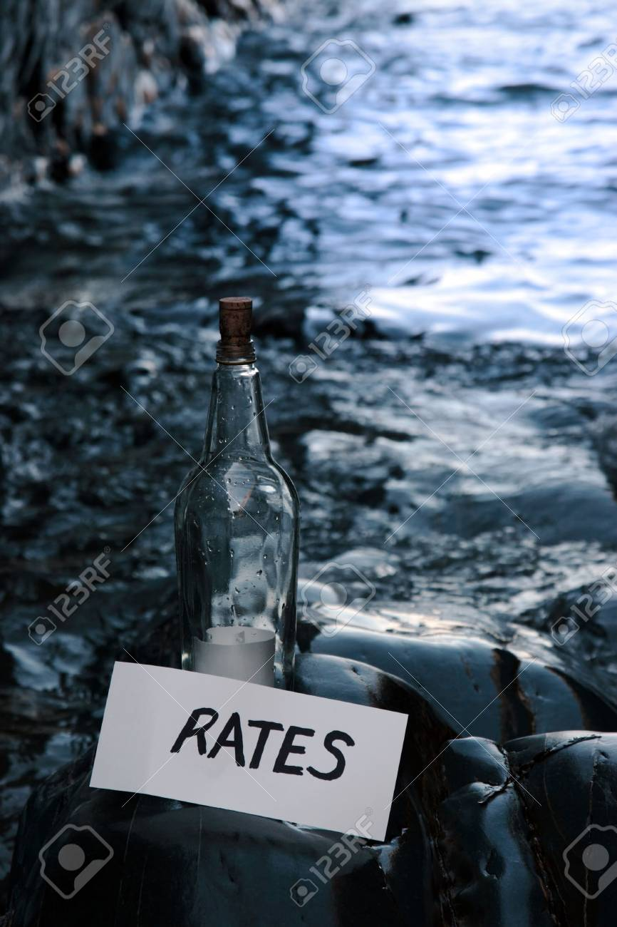 a bottle with a message on water rates standing on a rocky coastline Stock Photo - 5631762