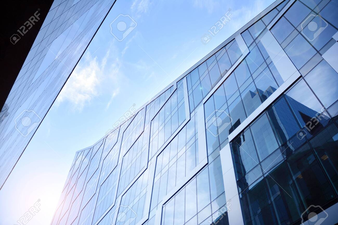Modern architecture with sun ray. Glass facade on a bright sunny day with sunbeams in the blue sky. - 138872550