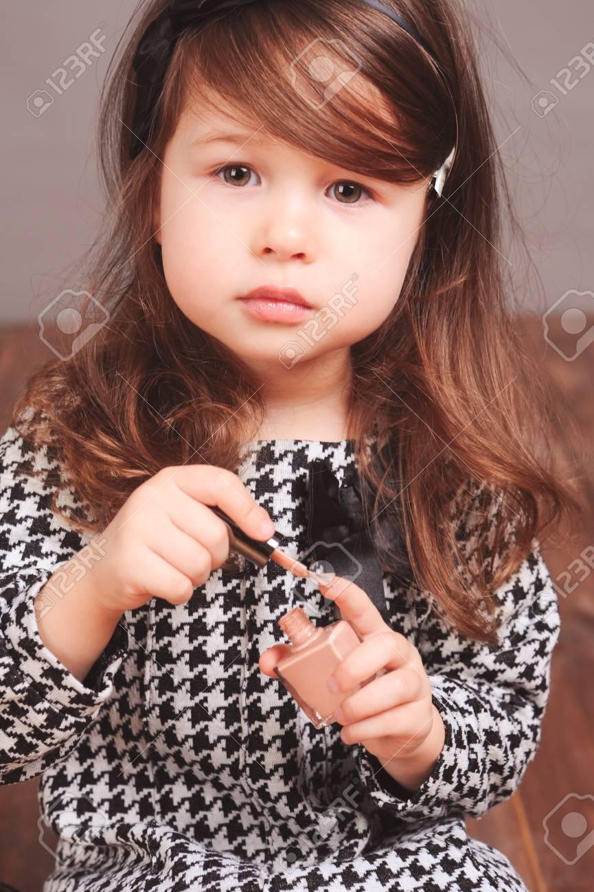 a557fb0fc Adorable niña de niño 3-4 años que juegan con los productos de maquillaje en