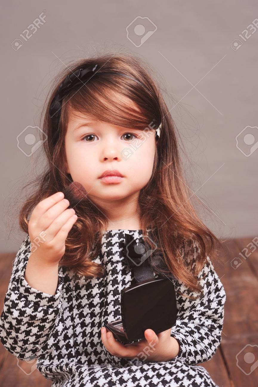Chambre Petite Fille 3 Ans belle petite fille 3-4 ans de poudre appliquer sur le visage dans la  chambre. en regardant la caméra. le port de robe élégante.