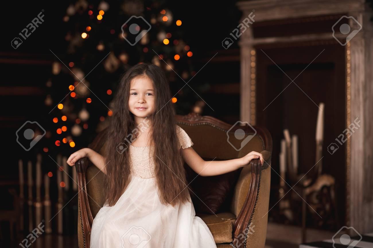 d235be2b64 Niña Sonriente 4-5 Años De Edad Con Un Vestido Blanco De Moda Sentado En La  Silla De La Vendimia En La Habitación Sobre El árbol De Navidad Con Luces.