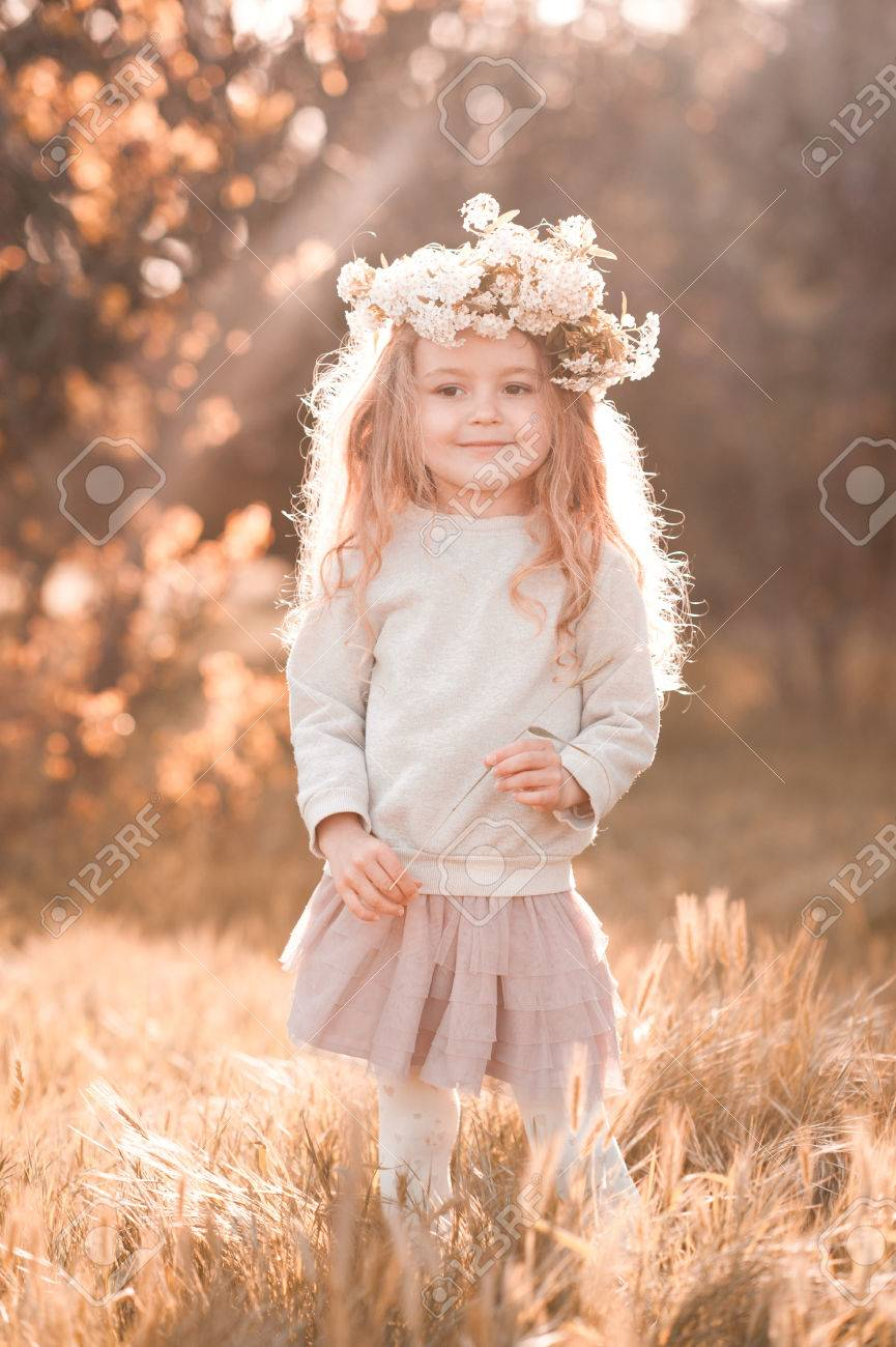 cute baby girl 4-5 year old walking in park wearing flower wreath