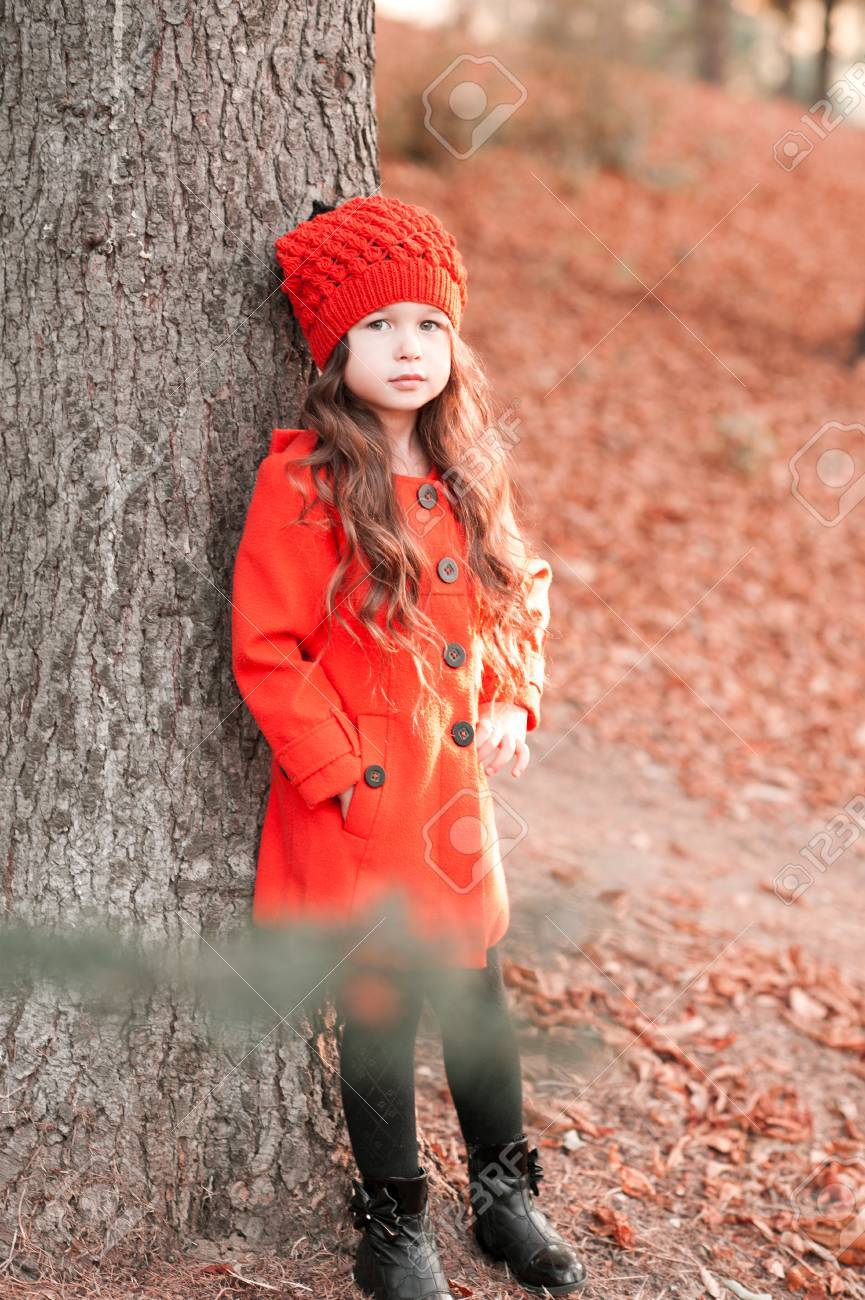 b6c15184660f Stock Photo - Stylish baby girl 3-4 year old posing outdoors. Wearing  trendy winter coat and knitted hat outdoors. Looking at camera. Childhood.