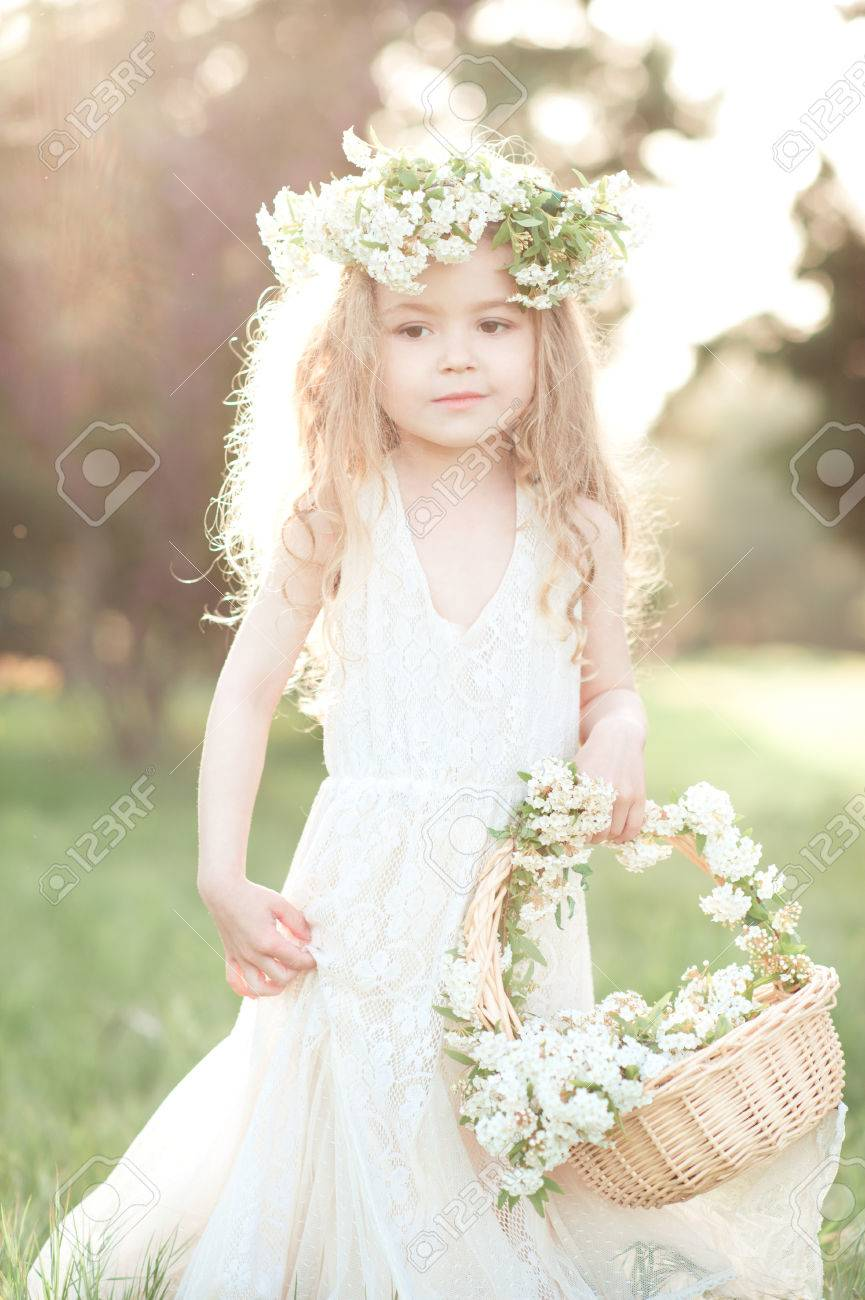 d61aeac3282ba Cute baby girl 3-4 year old wearing trendy white dress and floral wreath  outdoors