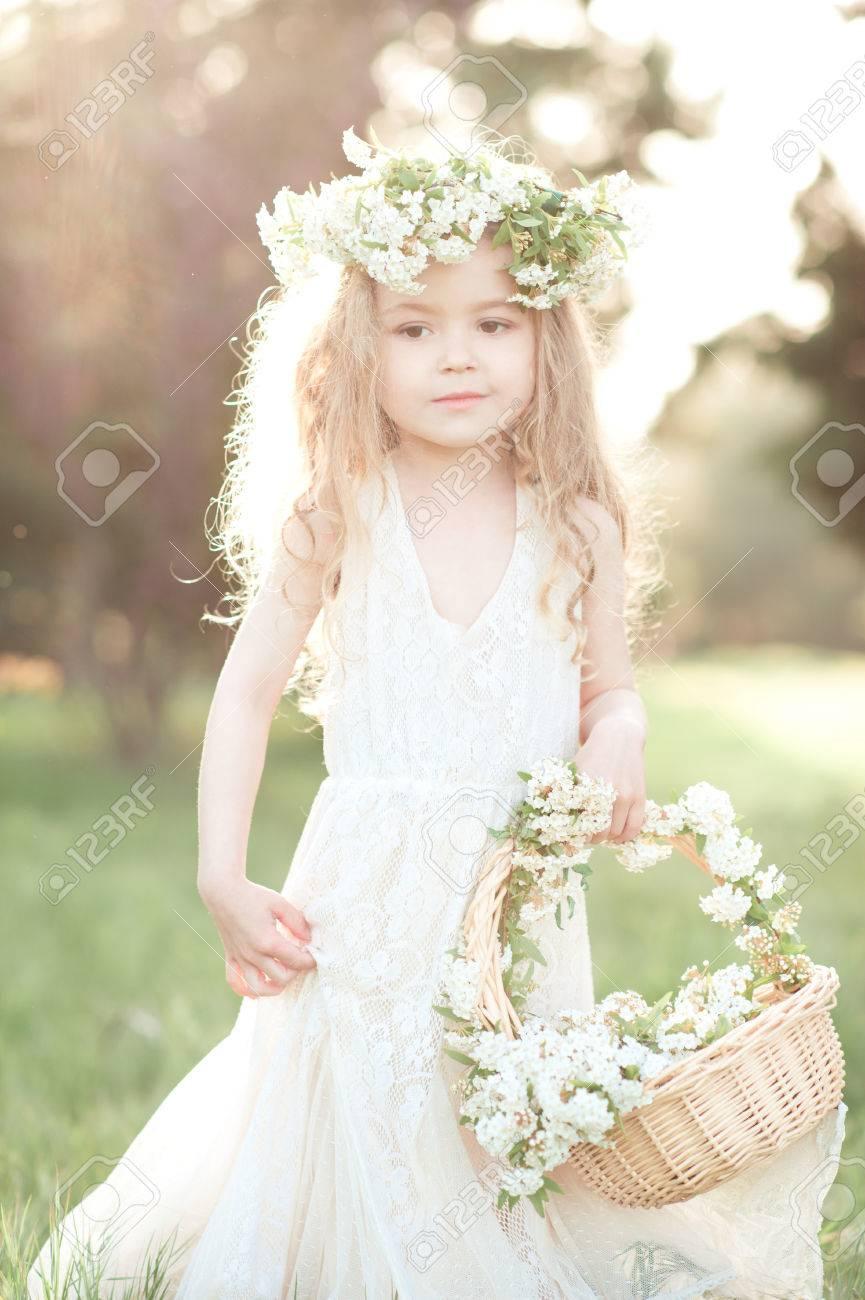 f0a2e0bd3d Linda niña de 3-4 años de edad con un vestido blanco de moda y la corona de  flores al aire libre. Celebración de la cesta de flores. Infancia.