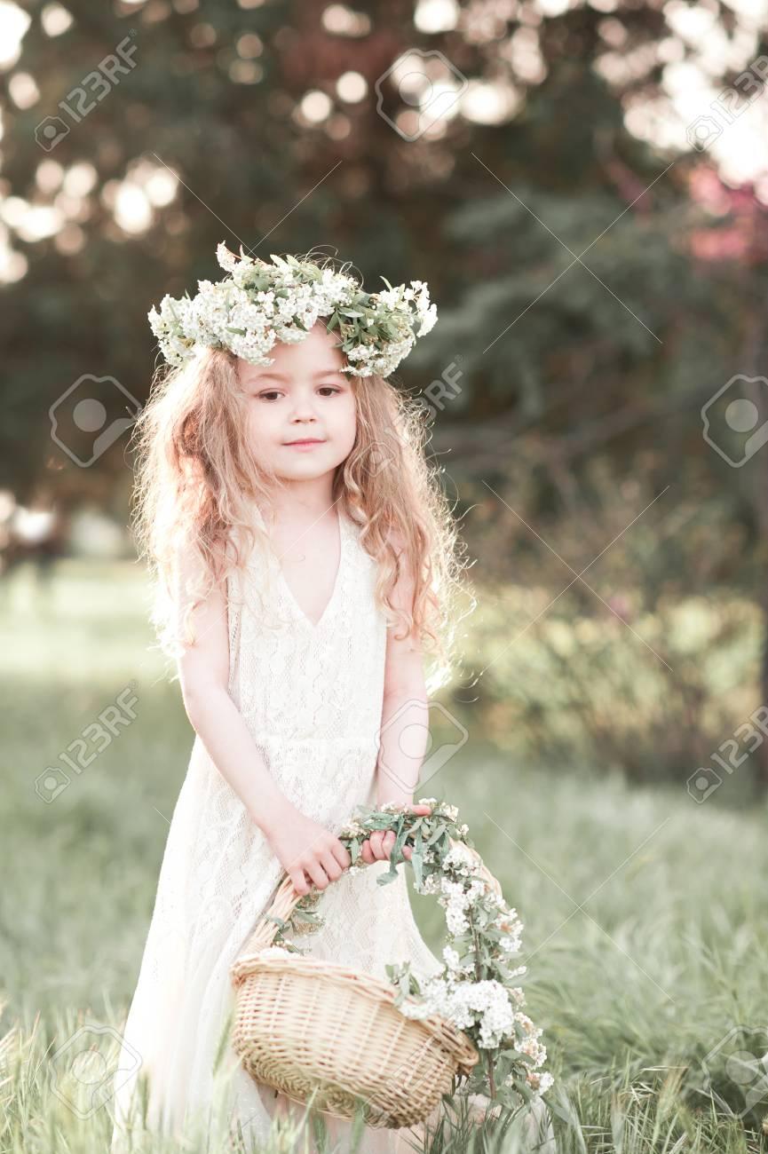2734d27019916 Banque d images - Belle petite fille de 4-5 ans debout à l extérieur.  Porter une robe blanche élégante et une couronne florale.