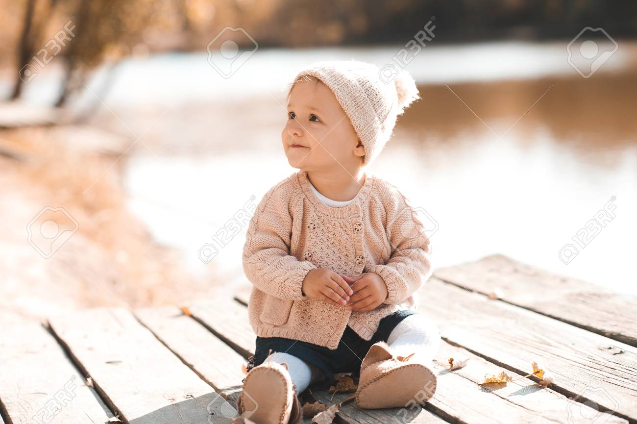 3699571e827f Smiling baby girl 1-2 year old wearing stylish knitted clothes sitting  outdoors. Looking