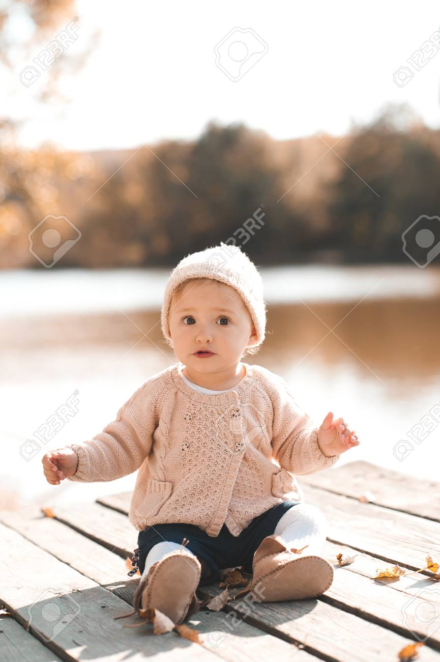 0815e8e8c2a10 Cute baby girl 1 year old wearing stylish knitted clothes posing in autumn  park outdoors.