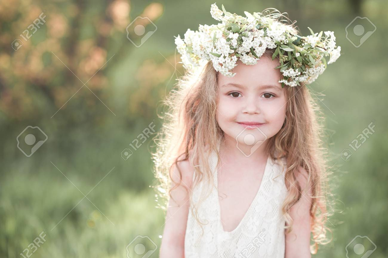 Smiling baby girl 4-5 year old wearing white dress and flower hairband over  nature ab07266c86b