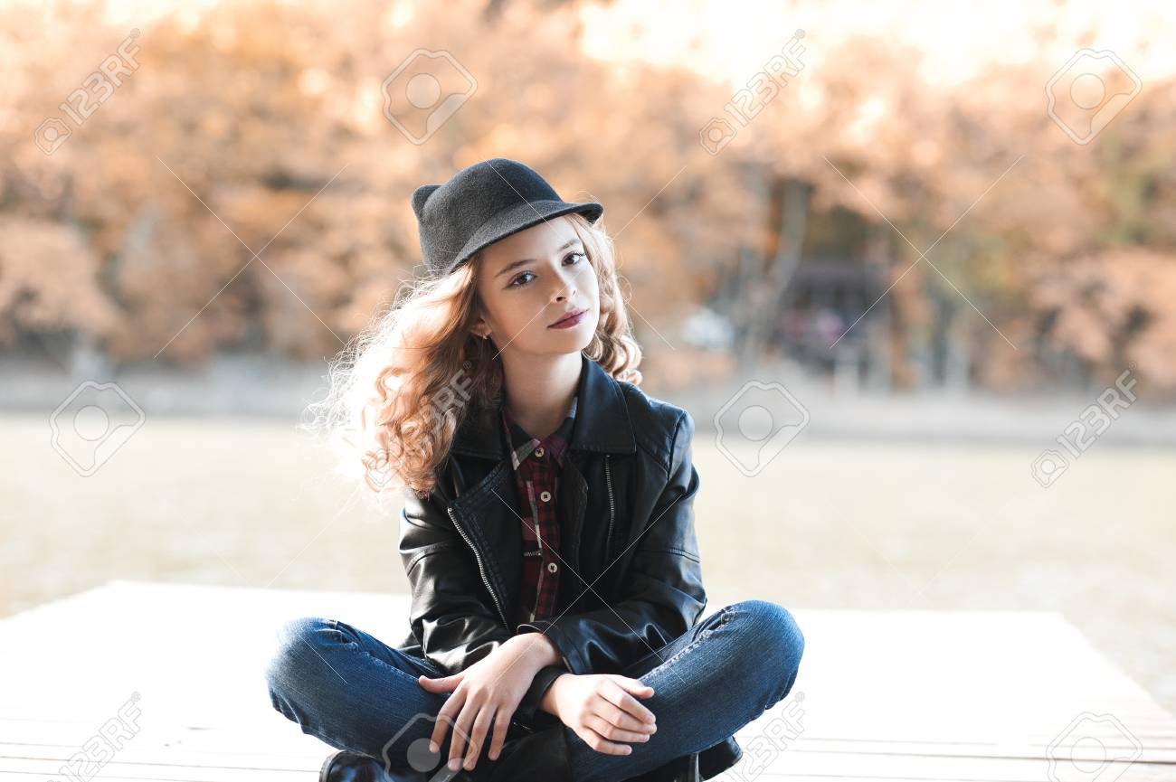 e849725d906 Stock Photo - Stylish teen girl 12-4 year old wearing trendy casual clothes  sitting outdoors. Looking at camera.