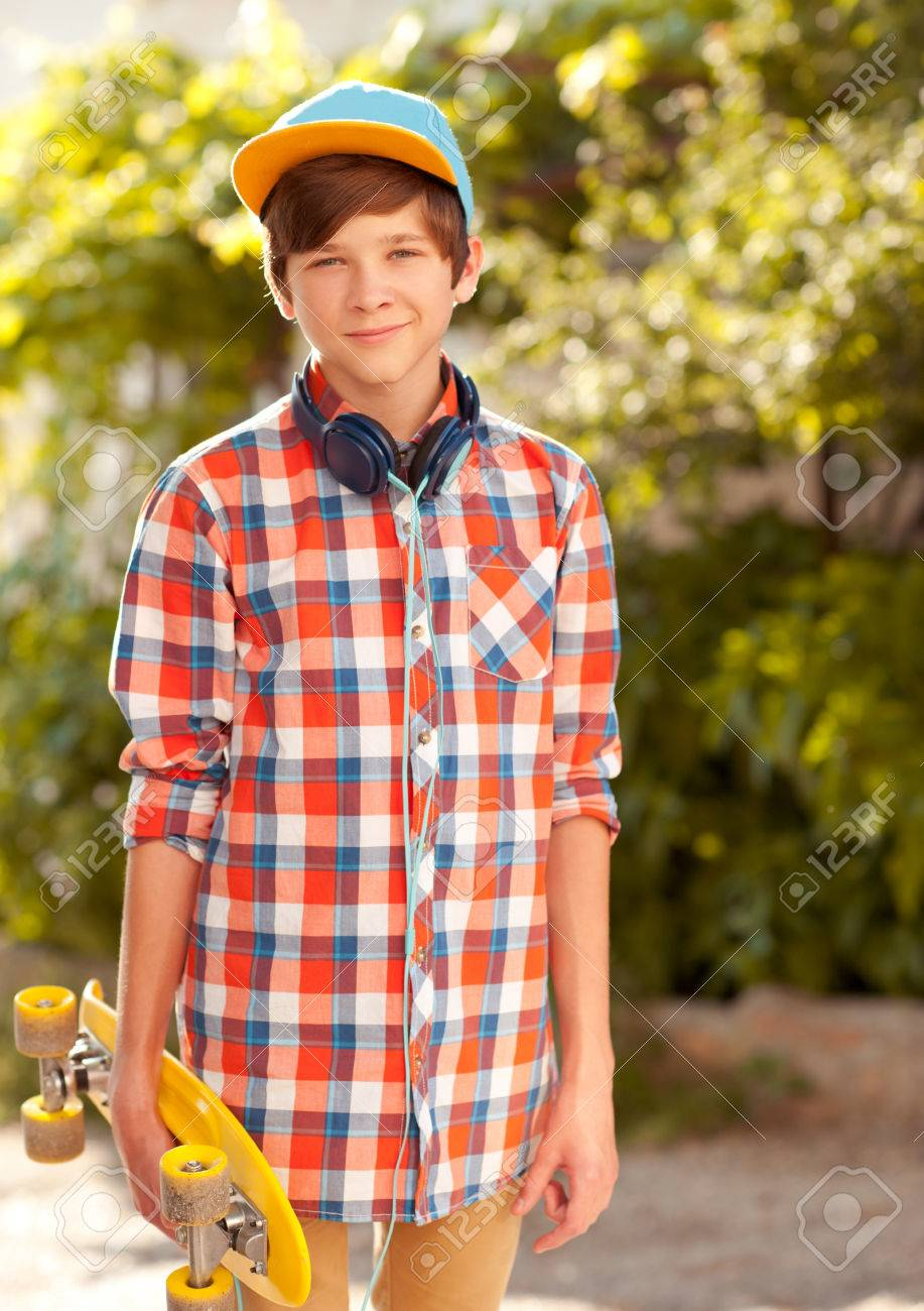 57d85af1f651 Stock Photo - Stylish kid boy 14-16 year old wearing trendy clothes.  Holding skateboard outdoors. Looking at camera.