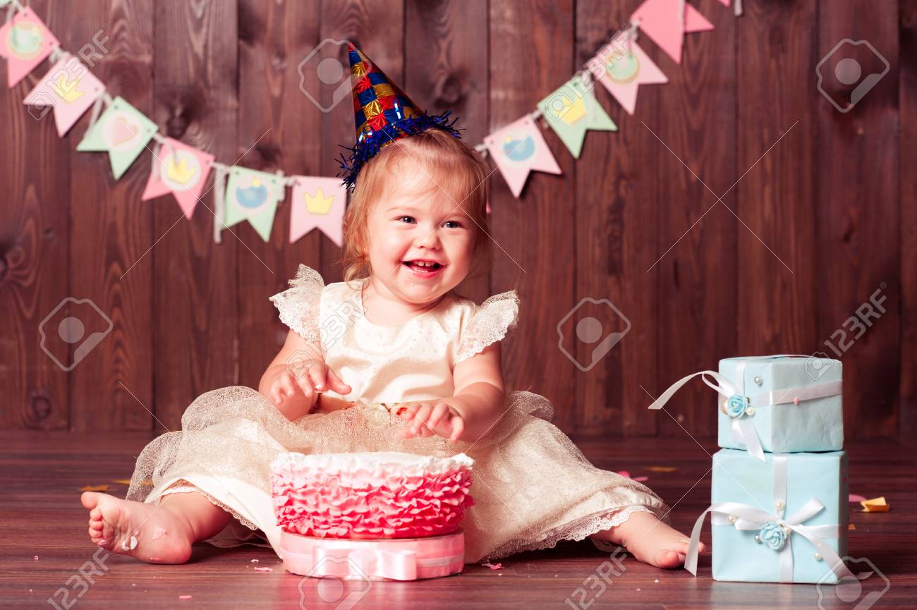 Laughing Baby Girl 1 Year Old Eating Birthday Cake In Room Wearing Princess Dress