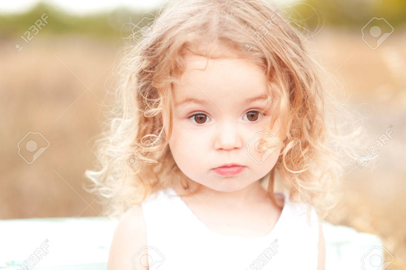 388037192f54 Cute baby girl with blonde curly hair outdoors. Little girl 2-3 year old