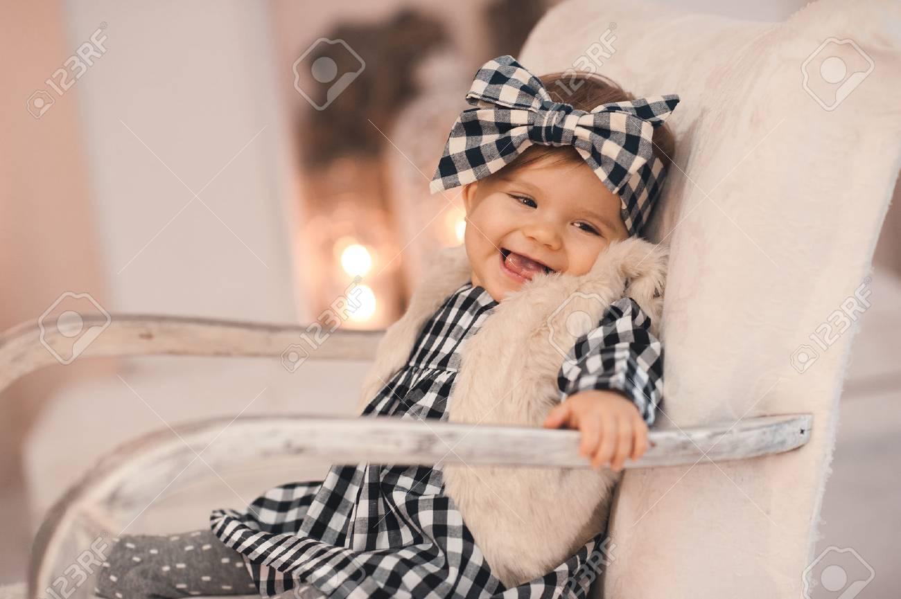 90d60666c2e Foto de archivo - Risa con estilo bebé niña menor de 1 año con ropa de moda  sentado en blanco vintage silla en la habitación sobre la chimenea blanca.